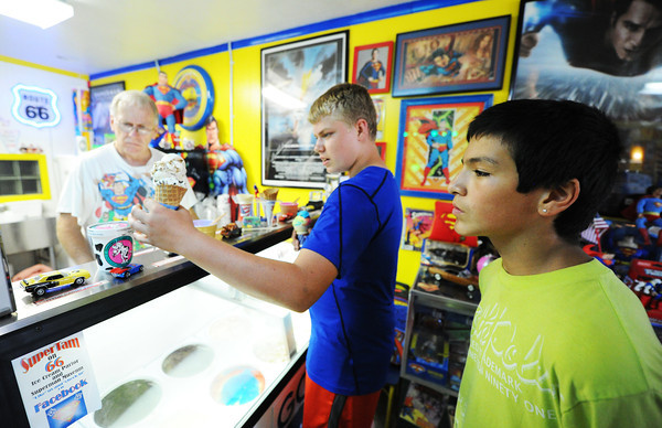 """Globe/T. Rob Brown<br /> Owner Larry Tamminen (left) takes and fulfills ice cream orders from customers Mason Jones (center) and Bobby Acevedo, both 14 and of Carterville, Tuesday evening, July 23, 2013, at SuperTam on 66 in Carterville. SuperTam on 66 is an ice cream parlor and Superman museum. """"We've been coming here since we were kids,"""" Acevedo said."""