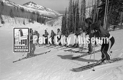 A ski instructor stands before ten students at the Park City Mountain Resort, ca.1974 (Image: 1999-4-218, Park City Mountain Resort Collection)