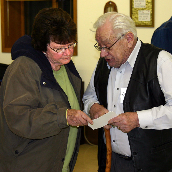 """Cheryl Miller and Linfred Schuttler swap information about an old Spearfish photograph.  Such discussions and fellowship are an important part of the SAHS gatherings.  For more information about the society -- including a membership form -- visit our <a href=""""http://www.spearfishhistory.org""""> Spearfish Area Historical Society</a> web site."""