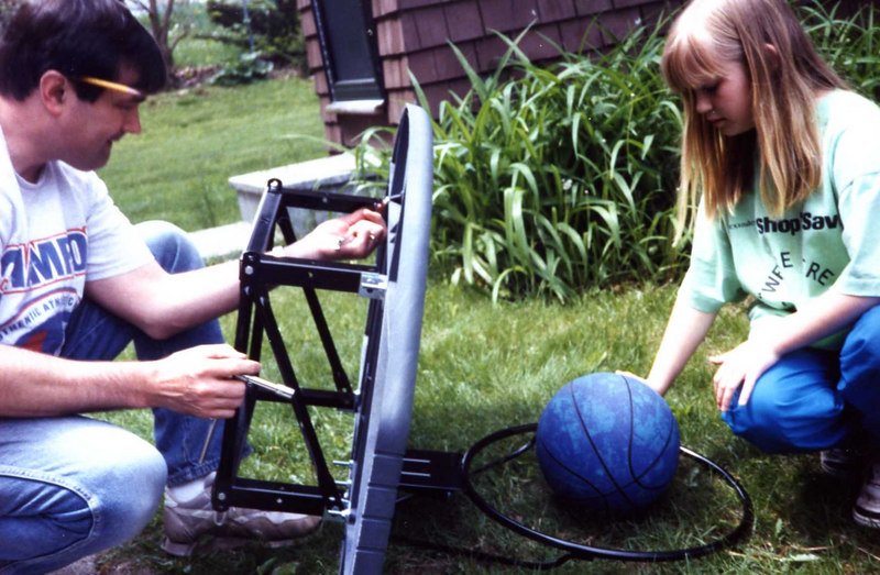 Keith and Janine Stickney putting up the basketball hoop over the garage.