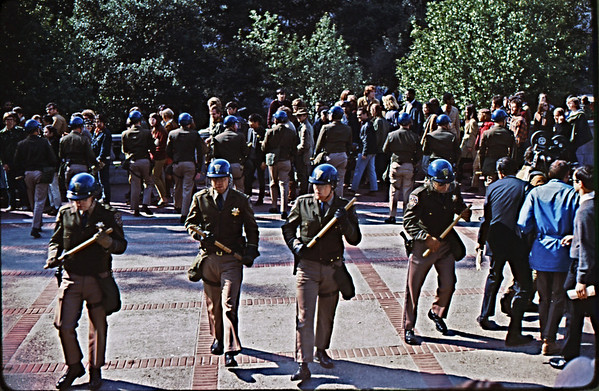 5*Thu, Feb 13, 1969<br /> *People: 2 lines of cops<br /> Subject: <br /> *Place: Sather Gate<br /> Activity: twlf<br /> Comments: students trapped, pandemonium among press.  Look at faces.