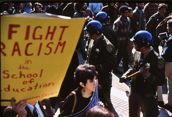 4*Thu, Feb 13, 1969<br /> *People: crowd, line of cops<br /> Subject: poster<br /> *Place: <br /> Activity: twlf<br /> Comments: black person in background (one of few seen in those days)