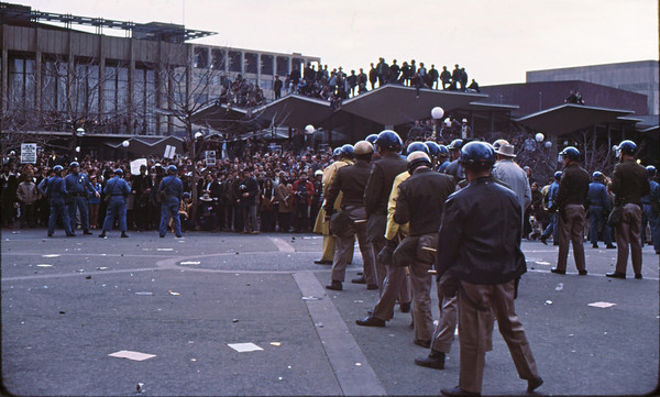 4*Wed, Feb 19, 1969<br /> *People: cops in Vee<br /> Subject: <br /> *Place: sproul plaza<br /> Activity: twlf<br /> Comments: just before rush into crowd to arrest protester.  Spectators on roof.  Notice that the vee formation of the cops is repeated in the roof line.  Artsy!