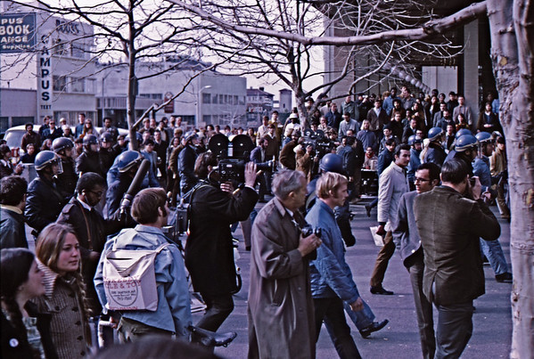 "4*Thu, Jan 30, 1969<br /> *People: cops, crowd, photogs<br /> Subject: wedge formation<br /> *Place: Sproul Plaza at Bancroft<br /> Comments: 1st cops on campus since the FSM (1964-5).  Backpack states ""Berkeley Cycle and Toy""  2300 ?? Shattuck Ave TH5-7560 - long gone. I followed the press a lot since they seem to know what was about to happen."