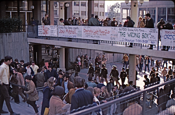 "4*Thu, Feb 13, 1969<br /> *People: cops, crowd<br /> Subject: <br /> *Place: coming up from Lower Sproul Plaza<br /> Activity: <br /> Comments: students running.  Notice sign for Joni Mitchell: Both Sides Now, Circle Game, Woodstock  I was 25.  She was 26. 1st album 3/68. 2nd, ""Clouds"" 4/69, Grammy 4/70"