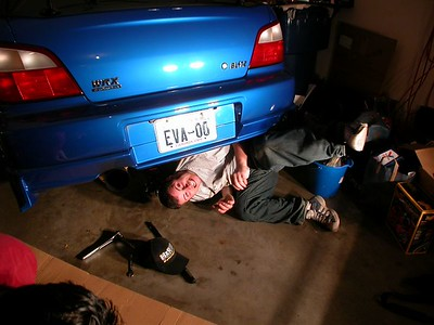 Kevin using his small stature to get underneath my car to install my Espelir catback at Tanya and Marcel's house