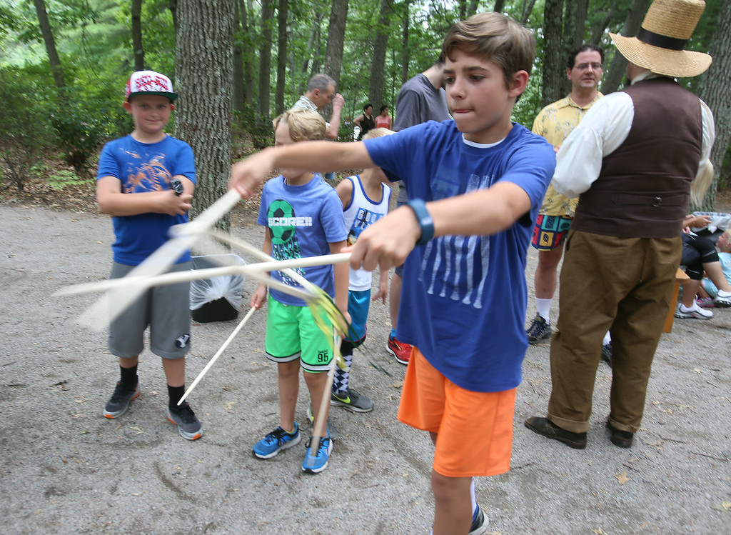 ". DCR celebrate Henry Thoreau\'s 200th birthday with ""Henry\'s Watermelon Party\"" at Walden Pond State Reservation.  Ethan Funk, 13, of Acton, plays The Game of Graces, throwing the ring by moving the sticks apart. The 19th Century game was supposed to make girls graceful. (SUN/Julia Malakie)"