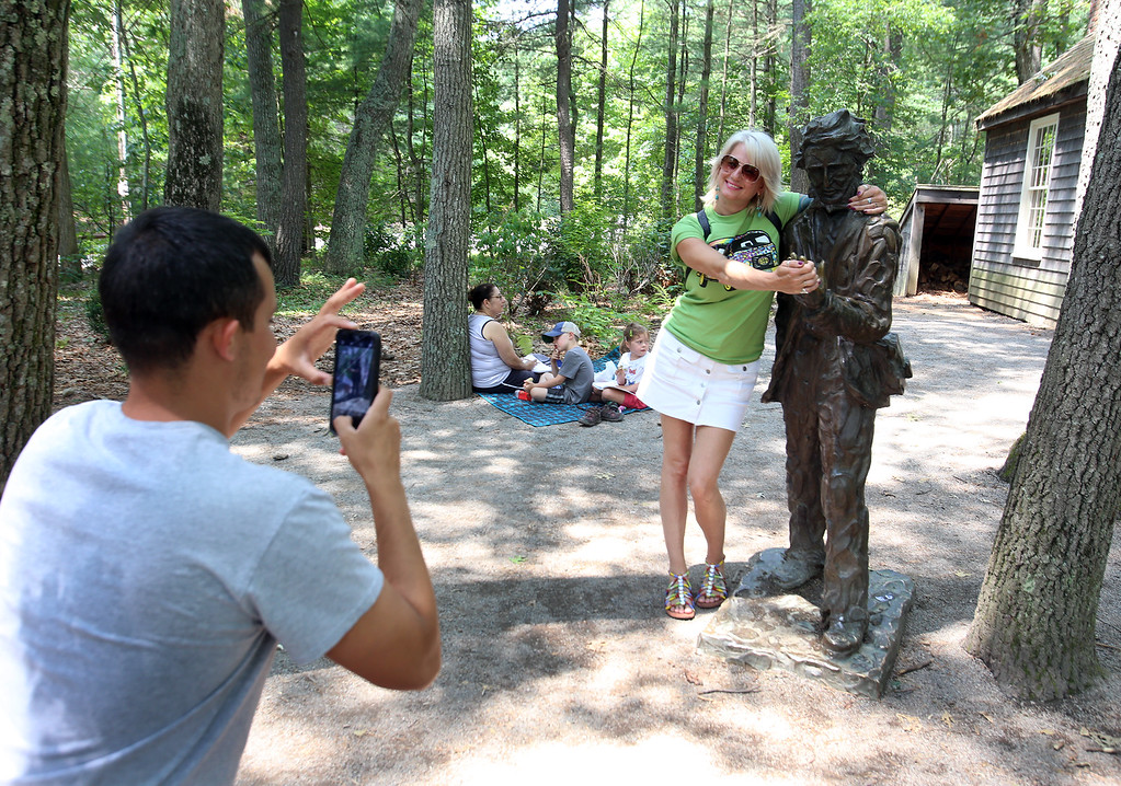 ". DCR celebrate Henry Thoreau\'s 200th birthday with ""Henry\'s Watermelon Party\"" at Walden Pond State Reservation. Jennifer Lewis of Little Rock, Arkansas, poses for a photo with the Thoreau statue. She said \""I had no idea this was his birthday. He was my favorite writer\"" when she studied literature in college. Her son Jori Aldridge of North Andover, left, is a student at Mass College of Pharmaceutical Health Sciences. (SUN/Julia Malakie)"