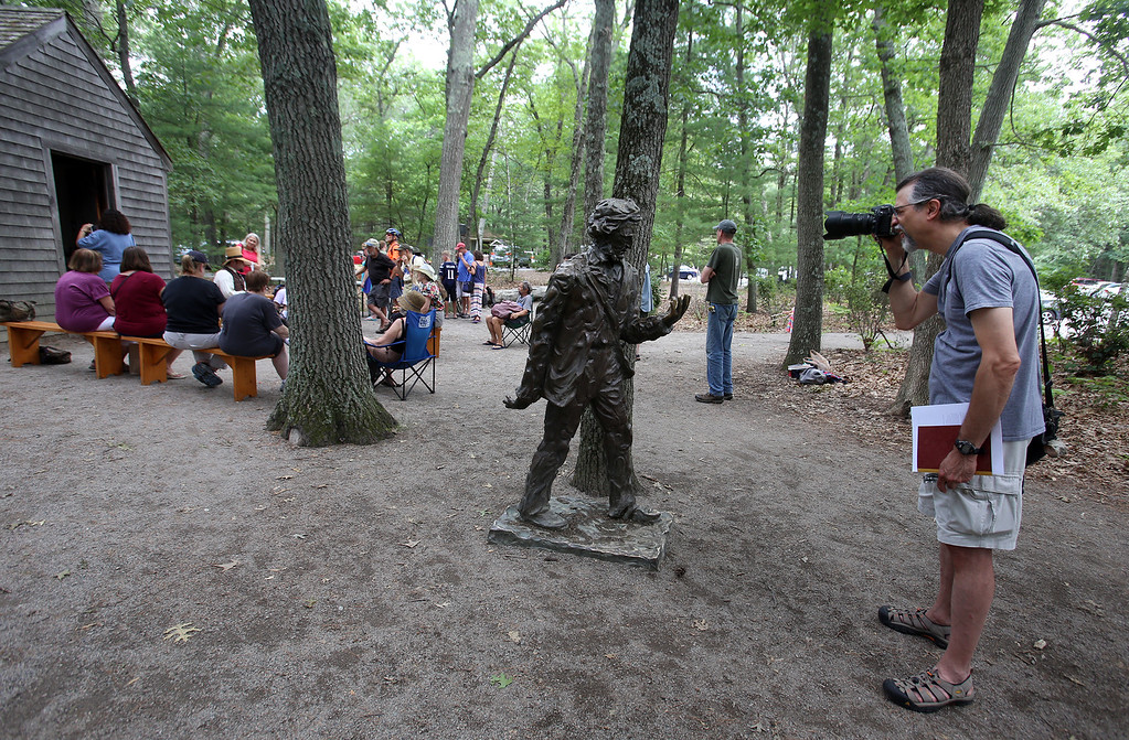 ". DCR celebrate Henry Thoreau\'s 200th birthday with ""Henry\'s Watermelon Party\"" as historian Richard Smith of Acton portrays Thoreau at the replica house at Walden Pond State Reservation.  Gerry Katzban of Putnam Valley, N.Y., takes a picture of the Thoreau statue, with Smith in the background. Katzban had not known about the birthday, but was in the area dropping off his son at an MIT summer program. He said Thoreau \""is one of my heroes. I\'ve been meaning to come here for 30 years and this is the day I came. (SUN/Julia Malakie)"
