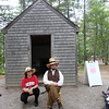 "DCR celebrate Henry Thoreau's 200th birthday with ""Henry's Watermelon Party."" Dawna Carrette of Concord kneels next to historian Richard Smith of Acton for a photo as he portrays Thoreau at the replica house at Walden Pond State Reservation.  (SUN/Julia Malakie)"