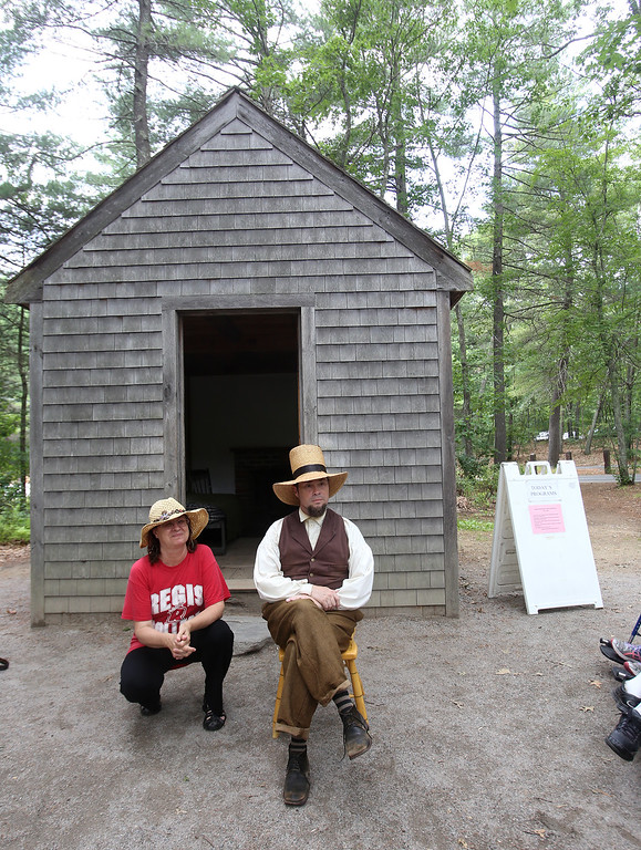 ". DCR celebrate Henry Thoreau\'s 200th birthday with ""Henry\'s Watermelon Party.\"" Dawna Carrette of Concord kneels next to historian Richard Smith of Acton for a photo as he portrays Thoreau at the replica house at Walden Pond State Reservation.  (SUN/Julia Malakie)"