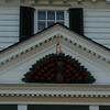 A traditional Williamsburg apple fan hangs above the front porch.