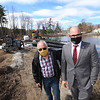 Tyngsboro assistant town administrator Justin Sultzbach, right, and Chaz Doughty, a member of the Planning Board, Master Plan Committee, and Community Preservation Committee, stand by the dam which is going to be reconstructed of concrete with a stone facing. Water is being pumped out of Upper Flint Pond to lower the water so that work can begin, after a coffer dam is built. JULIA MALAKIE/LOWELLSUN