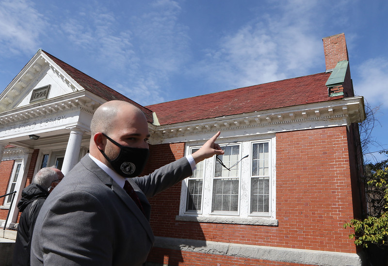 Tyngsboro assistant town administrator Justin Sultzbach points to the roof of the former Littlefield Library, one of the areas of pending improvements in Tyngsboro town center. The town plans to repair the roof, using red slate tiles from the rear of the building to replace damaged tiles on the front, and buying new red slate for the back, so any color mismatch will be less noticeable.  JULIA MALAKIE/LOWELLSUN