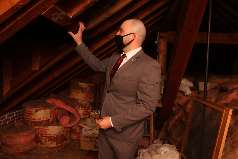 Tyngsboro assistant town administrator Justin Sultzbach notes the solid structure in the attic of the former Littlefield Libraryr. The mound at right is the top of the vaulted ceiling below. JULIA MALAKIE/LOWELLSUN