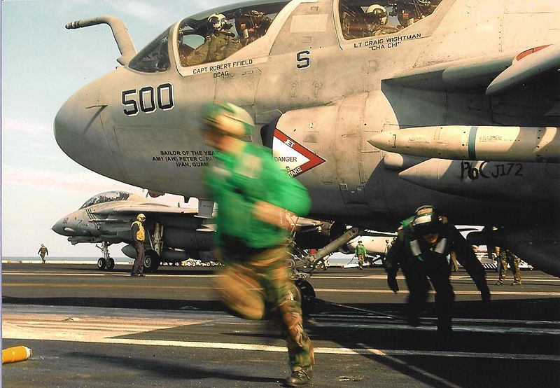 Flight operations crew hurrying to leave plane before catapult take off from the carrier.