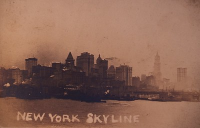 New York     Original Title: NEW YORK SKYLINE  Original Notes On the Back of Picture: This is a picture taken of NY from aboard our ship it certainly looked fine at night from far. It looks like a large mountain full of red lights of course from the buildings.