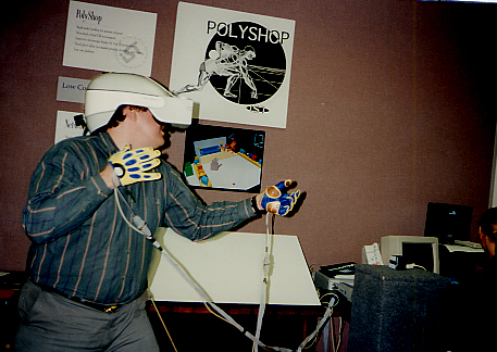 Dan Mapes: Head of the Toy Scouts, wearing Pinch Gloves he designed and sewed. In front of the PolyShop project poster that used his creations. ealry 1990s.