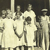 5. Bud and Nell's family about 1926 on the front porch of the St Louis Street house. From left, Maxine, Temple, Nell and Helen in front of her; Irene is tall, in the back and Mary is in front of her; then little John Barrett, then Dewey Stringer (who married Irene), then Bud and Pauline.