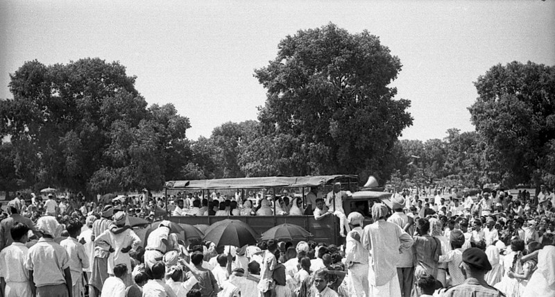 As soon as the procession came in view the orderly rows of people collapsed into a crush around the funeral vehicles. If I had kept my front row seat I might have been seriously hurt. Here a bus carrying family mourners pushes through the crowd.
