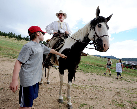 "Ofir Naor, 12, pets Sky, the horse, while ""Old Cowboy Fred"" talks about the early days on the ranch.<br /> Visitors at Walker Ranch Homestead saw what summer was like on a ranch in the 1800s in Boulder County. For more photos and a video of Walker Ranch, go to  <a href=""http://www.dailycamera.com"">http://www.dailycamera.com</a>.<br /> Cliff Grassmick  / July 29, 2012"