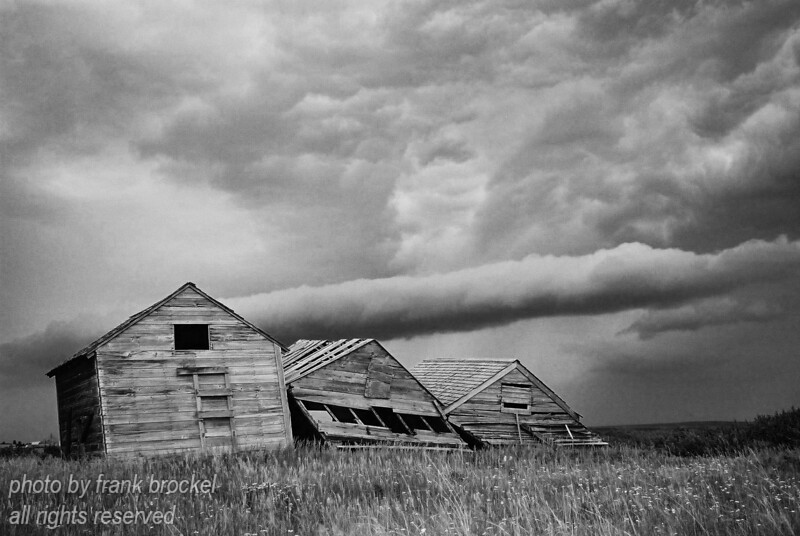 Thre old grain bins and a rolling cloud