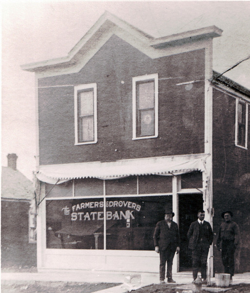 This is an undated photograph of the Farmers and Drovers State back that sat at the corner of Division and Missouri Streets where the old bank vault has stood alone for so many years.<br /> <br /> Thanks to Vern and Sharon Mizner for sharing this photograph.<br /> <br /> Click on the image to get a closer view of these gents -- and the building.<br /> <br /> Notice the utility line that attaches to the upper corner of the building.  We are told that the telephone switchboard was once located in the upstairs of the bank, so perhaps it's a telephone trunk line; however, it may well be a power line.  A water hydrant and fire plug appear to be in front of these three unidentified gentlemen.