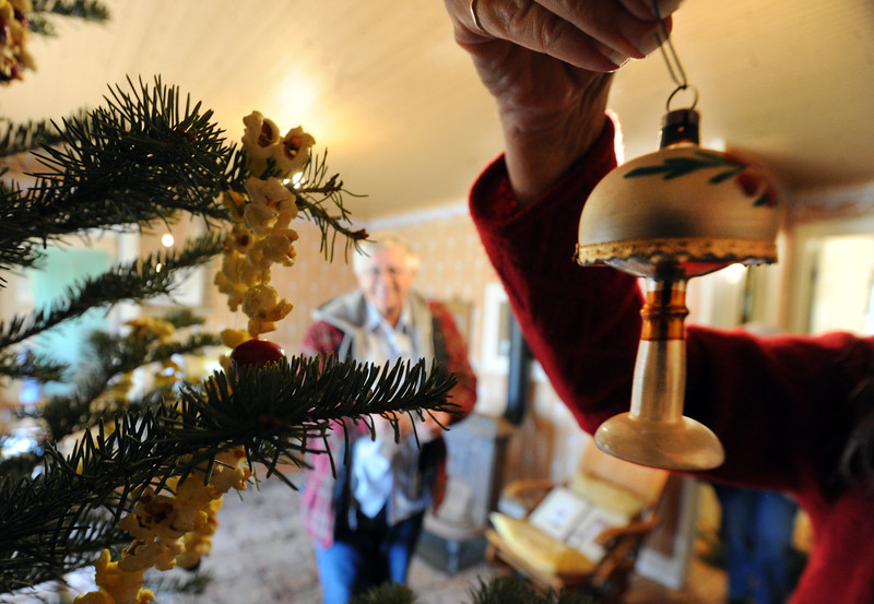"Carol Affleck puts up an ornament on the Wise Homestead Christmas tree on Friday.<br /> The Wise Homestead Museum in Erie is hosting a ""Homestead Christmas"", on Saturday, December 15th, 2012.<br />  For a video and more photos of the homestead, go to  <a href=""http://www.dailycamera.com"">http://www.dailycamera.com</a>.<br /> Cliff Grassmick  / December 7, 2012"