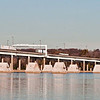 November 16, 2004:  In the river, two rows of concrete bases for the first bridge piers extend from the Maryland side.  In back, traffic continues to flow over the old bridge.
