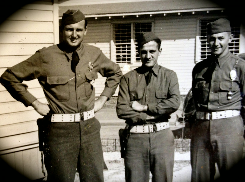 Here MP McClave (left) is with fellow comrades-in-arms. It could be that this is a POW camp in Rochester, because it appears as if the windows of the barracks in the background have bars on them.
