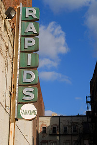 """These photos are inspired by one I found by Jake Wark here at Universal Hub blog.  The sign definitely has that 1950's look to it.  Faded from time and memory.  Does anyone know what the """"Rapids"""" was?  A nightclub back then?  A movie theater?  Or was it always just the name of the parking area?  I have these in History, as the general condition of the surrounding buildings make this area look due for the wrecking ball...or at the very least, the removal of this sign which filled me with enough fascination to expend the time and energy to go find it and photo it for myself.  It's located on New Chardon and Merrimac streets, nearby the Hurley building and the courthouse.  While I really like Jake Wark's version, I thought the saturation was a little too high.  In mine, aside from color correction and a little saturation boost, I wanted the drabness of the sign to convey the feeling that it is a faded icon of times past.  I think that a car was occupying the spot where Jake stood to get his; my angles are slightly different."""