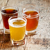 Three kinds of beer on old wooden background, selective focus