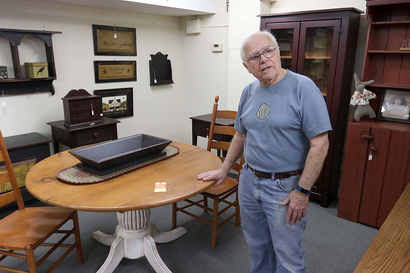 Dick Fiorentino owner of Hobart Village Mall Antiques talks about some of the reproductions on sale at his shop in Townsend. SENTINEL & ENTERPRISE/JOHN LOVE