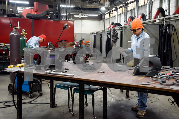 David Henderson and Beth Guinn work on their welding projects during a sculpture welding class at Tyler Junior College's west campus in Tyler, Texas, on Thursday, June 22, 2017. The class introduces students to the basics of welding and allows them to work on their own creative projects. (Chelsea Purgahn/Tyler Morning Telegraph)