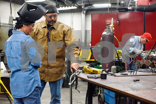 Caroline Sanchez listens as Ryan Henderson gives advice on her project during a sculpture welding class at Tyler Junior College's west campus in Tyler, Texas, on Thursday, June 22, 2017. The class introduces students to the basics of welding and allows them to work on their own creative projects. (Chelsea Purgahn/Tyler Morning Telegraph)