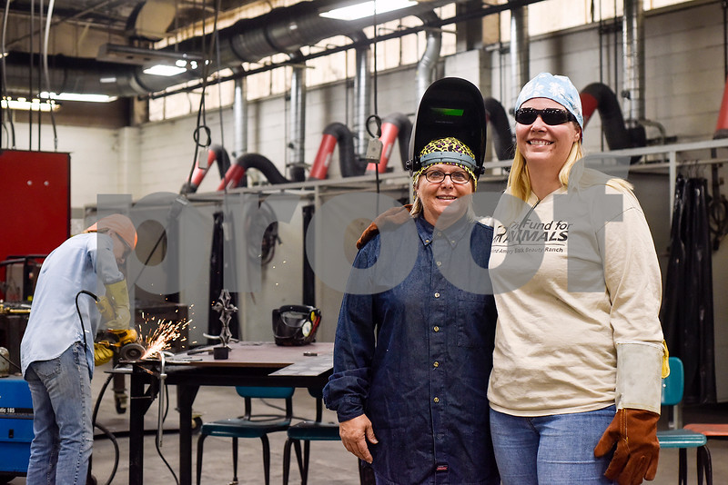 Wendy and Pamela Melser pose for a photo during a sculpture welding class at Tyler Junior College's west campus in Tyler, Texas, on Thursday, June 22, 2017. The class introduces students to the basics of welding and allows them to work on their own creative projects. (Chelsea Purgahn/Tyler Morning Telegraph)