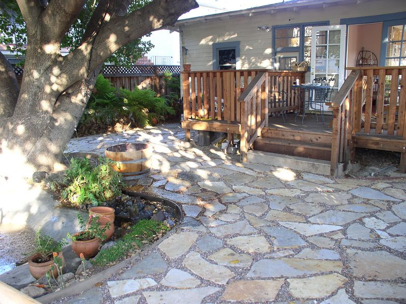 Back of house, with redwood deck and outrageous oak tree. Lower door goes to small unfinished basement with old but working washer/dryer.  Behind the shaded/flagstone area, the (deep) back yard has a lawn area with lavender, more flowering shrubs, and a very productive lemon tree.