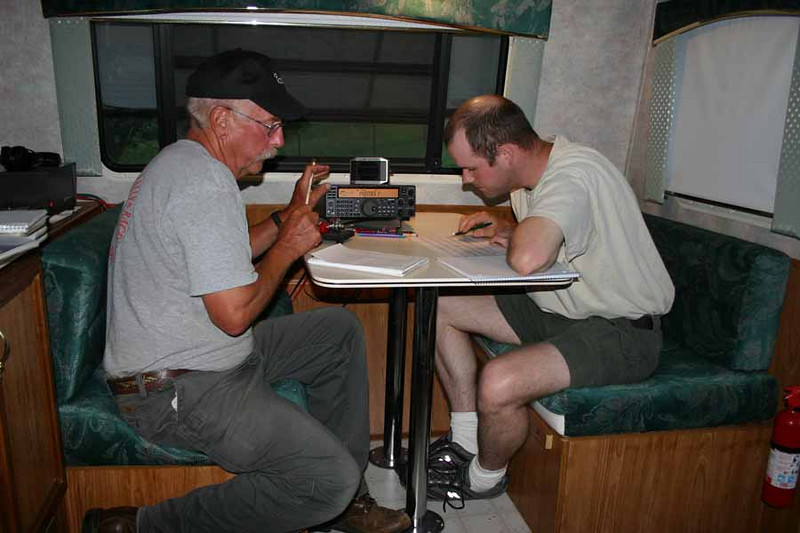 Inside his trailer, Don Matthesen, KØHP, teams up with Ryan Jennings, KCØGKF,  for late evening Field Day operations.