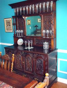 "Dining Room - This Welsh carved oak server is a marriage of an older piece with a newer top section. The bottom section was originally a vestment coffer, circa 17th century, with the following inscription below the doors: ""HEBB-DDUW  HEBB-DUIM"" which translates to ""Nothing Without God"". The top section and the hardware of the lower section were incorporated into the piece much later, probably in the 19th century."