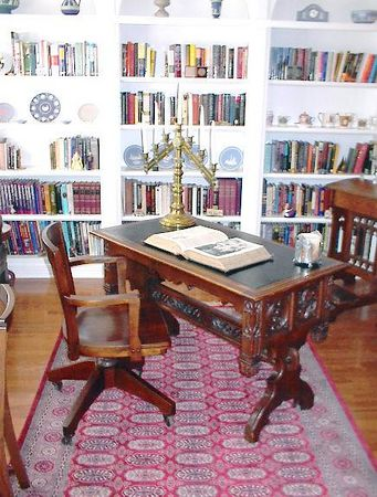"""Library - Gothic style walnut library table with leather top surface and elaborate pierced carving in the stretcher. Circa mid 19th century. The open bible on it is dated 1820. The gothic candleholder is from a church that """"went modern""""."""