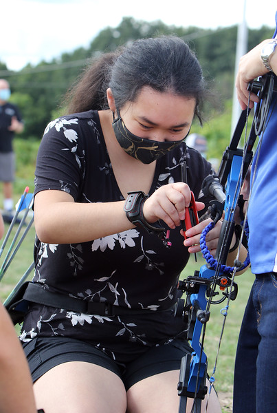 On Site Archery (owner Bob Wait of Billerica), holds classes Saturday mornings at Vietnam Veterans Park in Billerica.  Emily Michel, 15, of Arlington, figures out how to make an adjustment to her compound bow, using a set of Allen wrenches. (SUN/Julia Malakie)