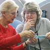 Knitting group at the Billerica Senior Center. Bess Clarke, left, helps newer knitter Liz Antoszewski figure out how to correct a mistake. Both are from Billerica. (SUN/Julia Malakie)