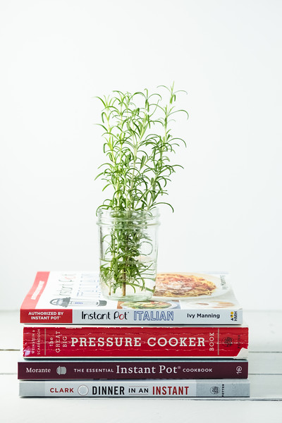 Instant pot cookbooks in a pile with a vase of rosemary