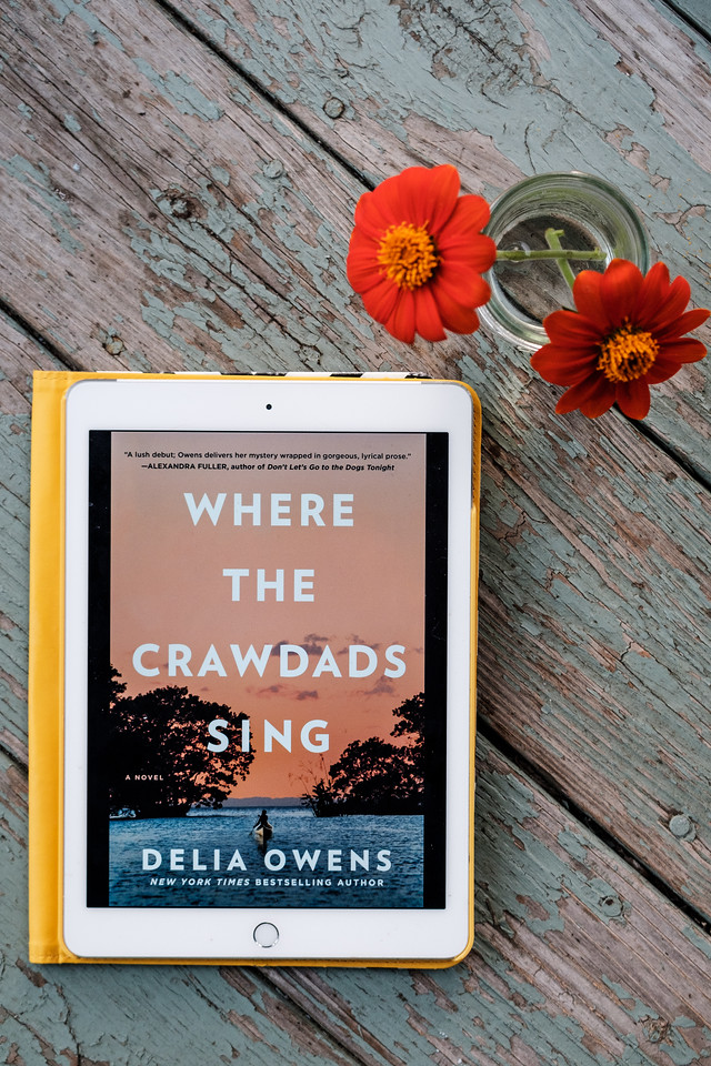 Where the Crawdads Sing by Delia Owens on ipad with flowers in a vase on distressed wood background.