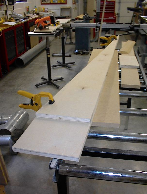 Here's one completed side sitting atop the remaining piece. This is why you start with an overlength board. After you have cut one, you just lay it over the other and cut the bottom of the second triangular board to produce two identical sides. Be very careful handling the sides before the cabinet is assembled; the pointed tops are very fragile.