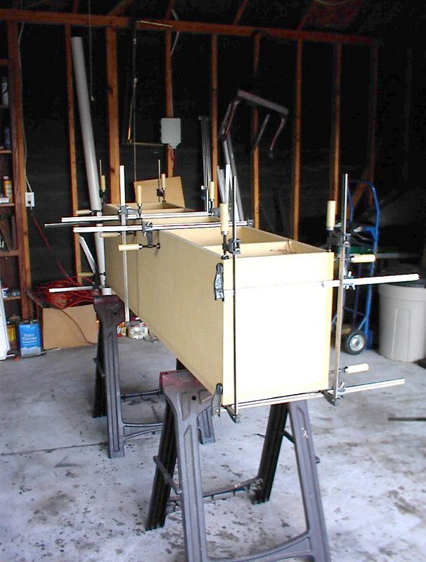 A completed enclosure, minus the back panel, in clamps.