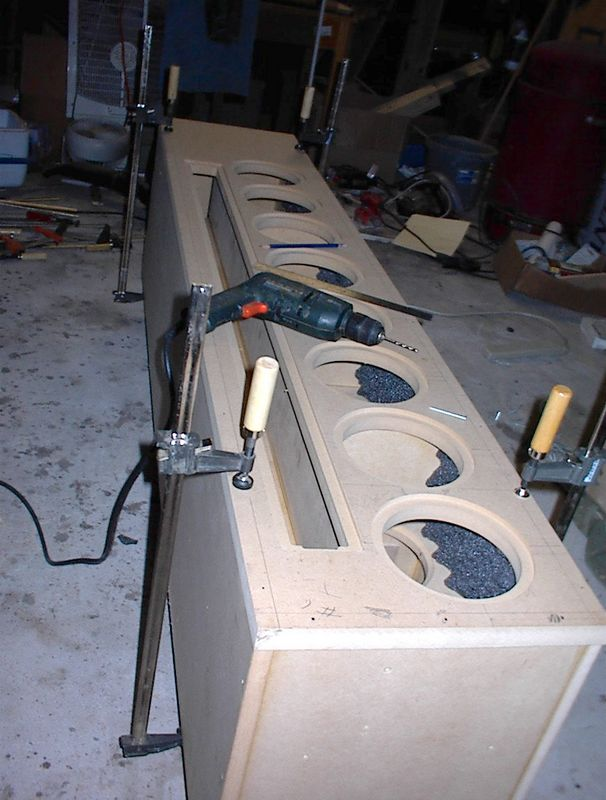 Attachng the baffle to the other enclosure. Hint: Clamp it near the four corners so that it overlaps the sides all around. Drill the pilot holes for the screws while it's clamped (or it may move while you're drilling). Remove it, apply glue, screw down tightly, wait until dry. Then (yet to be done with this one) you can use your router with a trim bit to trim it flush with the sides for a professional looking fit.