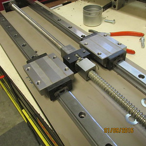 Ball screw and linear rails and trucks being mounted to base.