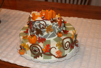 Fall themed topsy turvy cake.  Chocolate cake with vanilla frosting.  Chocolate fondant vines and acorns, vanilla fondant leaves and pumpkins.