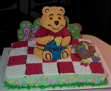 3D Winnie the Pooh baby shower cake.  Chocolate cake, cream cheese frosting; sugar cookie backdrop, frosting fruit/basket.